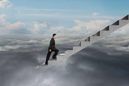 upward struggle: businessman climbing on concrete stairs with natural cloudy sky cloudscape background