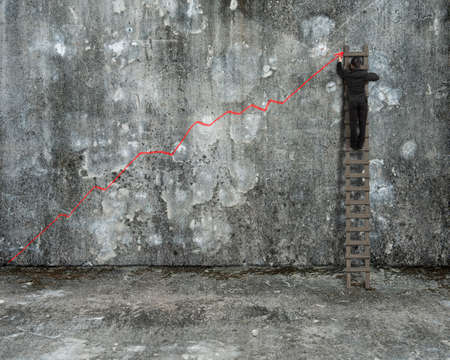 upward struggle: businessman climbing on ladder drawing red growth trend line on old mottled concrete wall and floor background