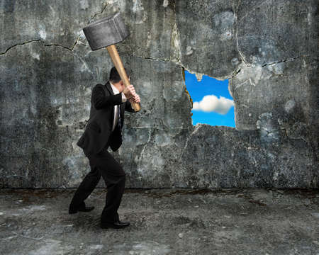 businessman hold sledgehammer cracking big hole discovered natural sky on concrete wall background Banco de Imagens