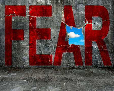 no fear: red FEAR word on grey grunge concrete wall with nature sky cloud view through big hole