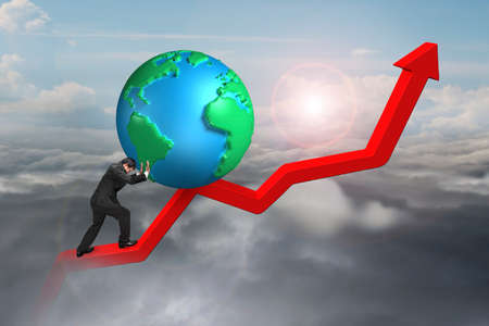 upward struggle: businessman pushing globe upward at starting point of red trend line with sunlight cloudscape background