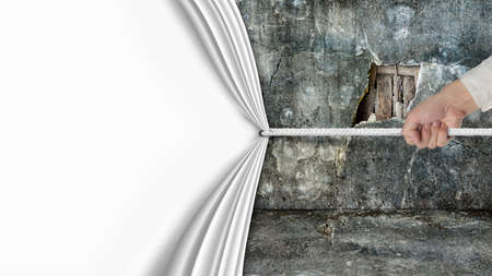 hand pulling open blank curtain covered old broken wall ruins isolated on white white background Stock Photo
