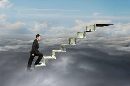 upward struggle: businessman climbing on money stairs with natural sky cloudscape background