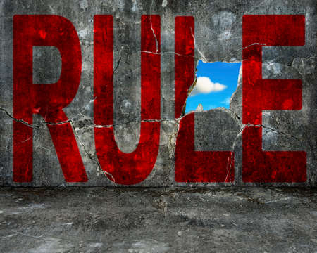 red RULE word on grey grunge concrete wall with nature sky cloud view through big hole photo