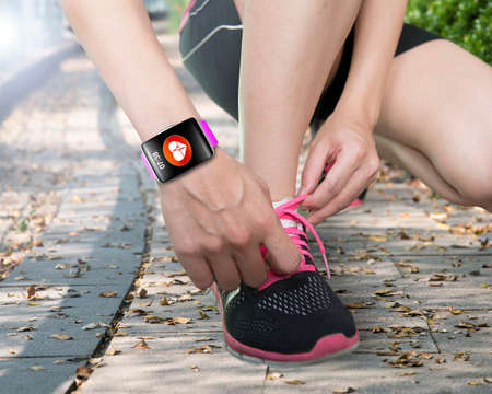 human hand tying shoelaces wearing bright pink watchband touchscreen smartwatch with red health icon on forest trail background Banque d'images