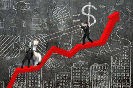 upward struggle: two businessmen moving 3D dollar sign upward on red trend chart with business concept doodles concrete wall background