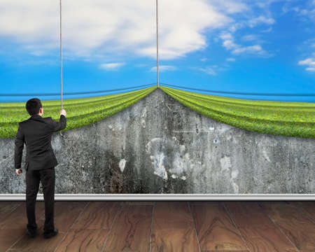 businessman pulling open sky curtain covered old mottled concrete wall on wooden floor background