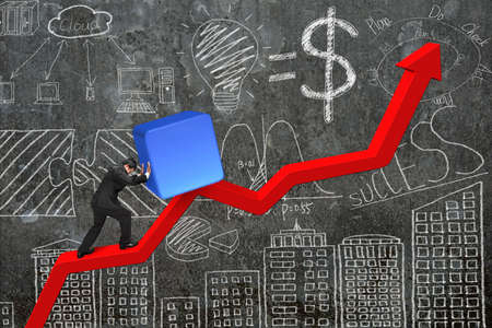 upward struggle: businessman pushing 3d block at starting point of red trend chart with  business concept doodles concrete wall background Stock Photo