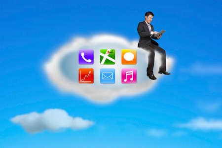 using tablet: businessman using tablet on app icons cloud with nature blue sky background
