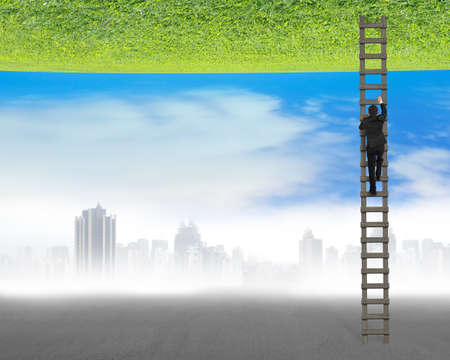 businessman climbing on ladder between two inverted world with gray cityscape and clean natural sky grass