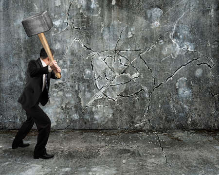 Hombre de negocios usando martillo agrietamiento del muro roto en ...