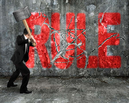 businessman using sledgehammer cracking red rule word broken on concrete wall background photo