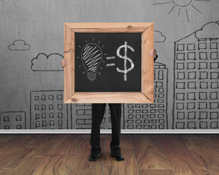 businessman holding blackboard with hand-drawn ideas equal money concept on cityscape doodles wall and teak wooden floor background photo