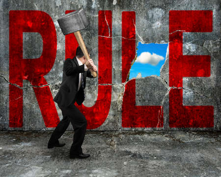 businessman holding hammer hitting red RULE word on concrete wall with nature sky cloud view through big hole photo