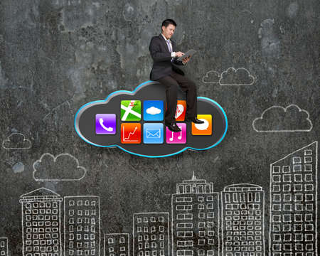 using tablet: businessman using tablet on black cloud with app icons and sky buildings doodles wall background