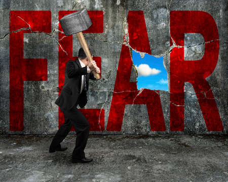 no fear: businessman holding hammer hitting red FEAR word on concrete wall with nature sky cloud view through big hole, overcoming fear concept.