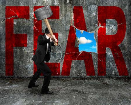 imprenditore in possesso di martello che colpisce parola FEAR rosso sul muro di cemento con la natura cielo vista nuvola attraverso grande buco, superando il concetto di paura.