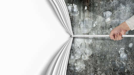 hand pulling blank curtain covered old dirty mottled concrete wall isolated on white background Banco de Imagens