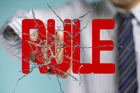 Business man hand hitting red rule word on cracked transparent glass photo