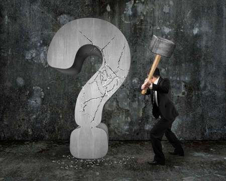 businessman holding hammer cracked question mark with gray mottled concrete wall background Banco de Imagens
