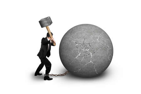 jail: businessman holding hammer hitting cracked concrete ball isolated on white background
