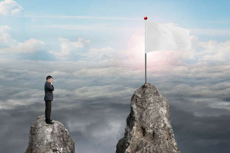 cloudscapes: Businessman standing on peak with blank white flag and natural sunlight cloudscapes background Stock Photo