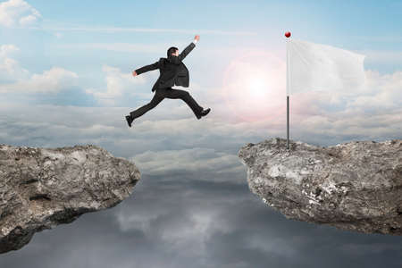 overcome a challenge: Businessman jump on cliff with blank white flag and natural sunlight cloudscapes background Stock Photo