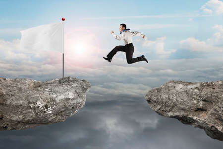 cloudscapes: Man jumping on cliff with blank white flag and natural sunlight cloudscapes background Stock Photo