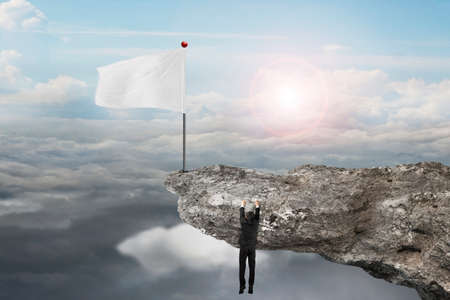 cloudscapes: man hanging on cliff with blank white flag and natural sunlight cloudscapes background
