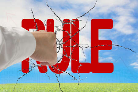 Man hand hitting red rule word on cracked transparent glass with nature sky grass background photo