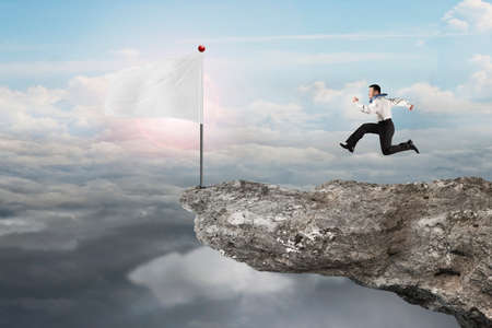 cloudscapes: man running to blank white flag on cliff with natural sunlight cloudscapes background Stock Photo