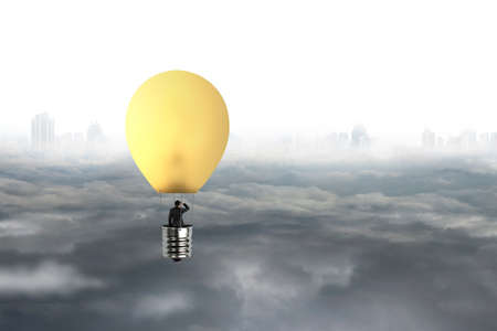 journey: Businessman in brightly yellow lamp hot air balloon flying over gray city sky cloudscape backgound Stock Photo