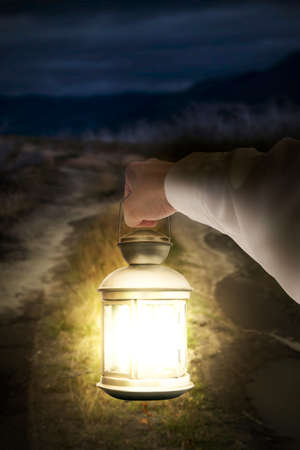 oil lamp: Right hand holding light illuminating dark road at night background Stock Photo