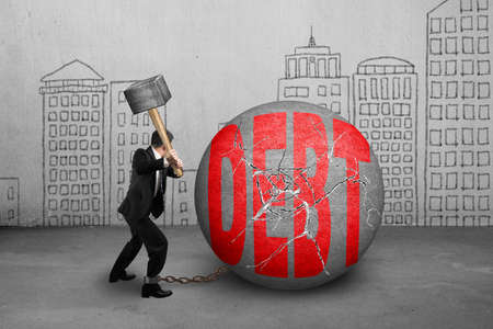 shackled: businessman holding hammer hitting cracked DEBT ball with city buildings doodles background