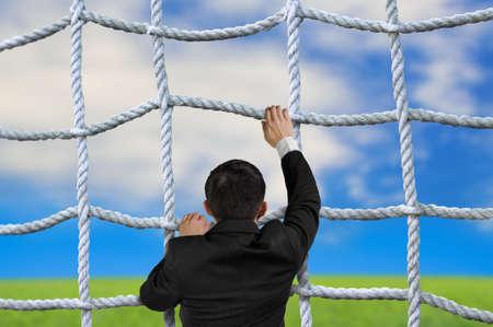 crisscross: Businessman climbing the crisscross rope net on natural sky cloud grass background