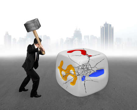 businessman holding sledgehammer hitting large dice with dollar sign and gray cityscape background photo