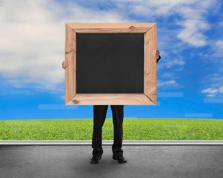 herbe ciel: Homme tenant vierge tableau noir avec naturel herbe ciel sur le plancher de b�ton