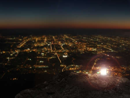 lit lamp: Lit lamp on rock mountain with city night view background
