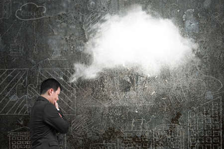 thinking cloud: Businessman thinking about white cloud thought bubble above his head with doodles wall background