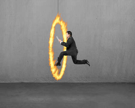 Businessman holding tablet jumping through fire hoop with concrete wall background photo