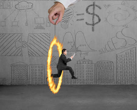 Businessman jumping through fire circle hand holding with doodles wall background photo