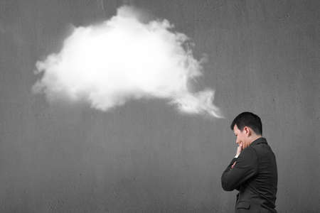 copy sapce: Businessman thinking about white cloud thought bubble above his head with concrete wall background