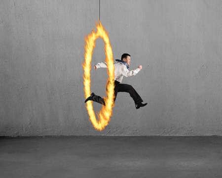Man springen door het vuur hoepel met betonnen muur achtergrond