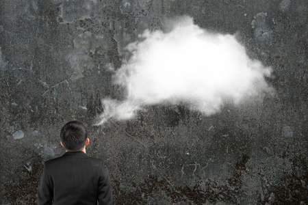 imagining: Man imagining white cloud thought bubble above his head with concrete wall background Stock Photo
