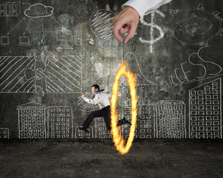 Man jumping through fire circle hand holding with doodles wall background photo