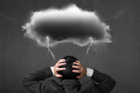 Depressed man with dark cloud rain lightning over his head, concrete wall background
