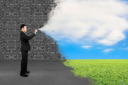 Businessman spraying natural clouds sky grass paint cover old brick wall background