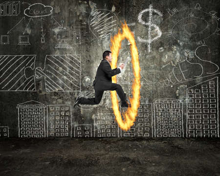 Businessman holding tablet jumping through fire hoop with doodles wall background photo