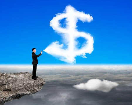 financial cliff: Businessman spraying dollar sign shape cloud paint on the cliff with cloudscape background