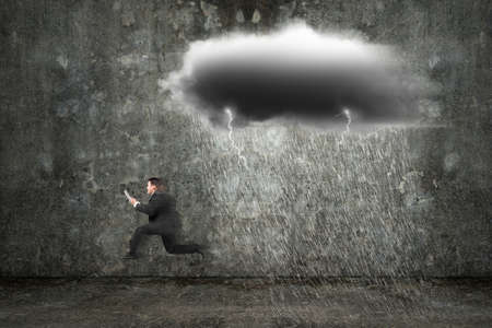 Running businessman holding tablet with dark clouds raining and lightning on concrete wall background photo